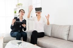Female buyer wearing virtual reality technology. Happy pretty female buyer wearing virtual reality technology device looking at 3D house simulation video and Royalty Free Stock Photo