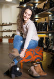 Female buying winter women shoes. Smiling female buying winter woman shoes in a shoe store royalty free stock photos