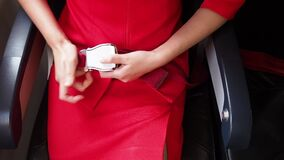 Female cabin crew in red uniform fasten seatbelt in aircraft.