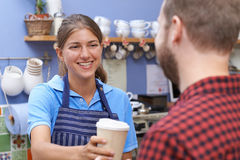 Female Cafe Worker Serving Customer With Takeaway Coffee Royalty Free Stock Photos