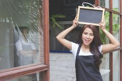 Female cafe worker smiling and holding blank blackboard Royalty Free Stock Photos
