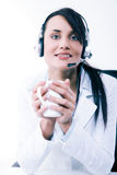 Female call center service operator at work. Attractive female helpdesk employee with headset at workplace Stock Image