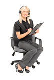 Female call service operator writing on clipboard Stock Photo