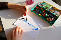 Female calligrapher creates inscription for sale, using brushes Royalty Free Stock Images