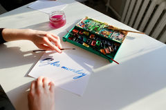 Female calligrapher creates inscription for sale, using brushes Royalty Free Stock Photo