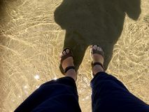 Female camino pilgrim cools her feet in a pool of sea water. stock photos