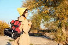 Female camper with backpack and sleeping bag in wilderness. Space for text royalty free stock images