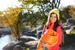 Female camper with sleeping bag near beautiful lake. Space for text stock photo
