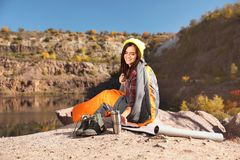 Female camper with thermos in sleeping bag. Outdoors stock images