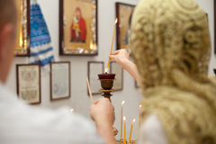 Female and candle in church. Young female looking at candle flames in church during praying Royalty Free Stock Photos