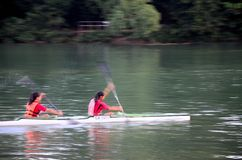 Female canoe paddlers row in lake Stock Images