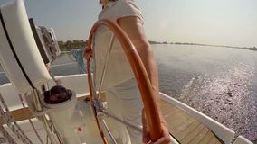 Female captain steering boat at sunset. Sailing, yachting, sport. Stock footage stock video footage
