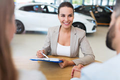 Female car dealer in showroom Royalty Free Stock Photo