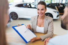 Female car dealer in showroom Stock Photos