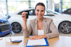 Female car dealer in showroom Royalty Free Stock Image