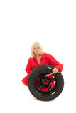 Female car mechanic with wheel Royalty Free Stock Photography