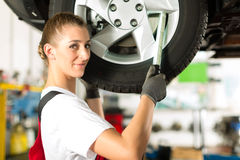 Female car mechanic working on jacked auto. Young woman as female car mechanic working on an auto in workstation royalty free stock image