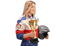 Female car racer holding a trophy. Studio shot of a female car racer holding a trophy and a helmet isolated on white background royalty free stock images