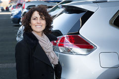 Female car seller holding car . Caucasian saleswoman in coat. Auto rental or sales concept. Royalty Free Stock Image