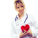 Female cardiologist with red heart. Periodic examinations. Cardiology concept. Female cardiologist holding red heart. Middle aged doctor with stethoscope and stock photos