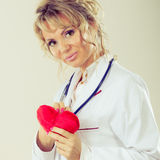 Female cardiologist with red heart. Periodic examinations. Cardiology concept. Female cardiologist holding red heart. Middle aged doctor with stethoscope and stock photo