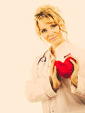 Female cardiologist with red heart. Stock Photo