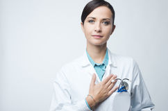 Female cardiologist touching with hand on chest Stock Images