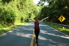 Female carefree backpacker in the middle of the forest on asphalt road. Tourist traveler feelings free looks fly on empty street. In Pico do Jaraguá, Brazil stock image