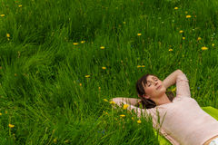 Female carefree spring start. Relaxing female lying in high grass stock image