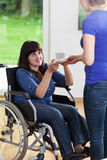 Female caregiver giving cup of tea to woman on wheelchair Stock Photo