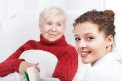 Female caregiver reading book Stock Image