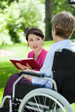Female caregiver reading book with senior woman Royalty Free Stock Image