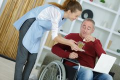 Female carer giving medicine to senior man at home royalty free stock images