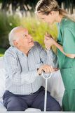Female Caretaker Helping Senior Man To Get Up From Stock Images
