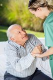 Female Caretaker Helping Senior Man To Sit On Royalty Free Stock Photography