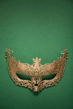 Female carnival golden mask on green background. Royalty Free Stock Photos