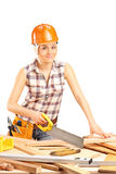 Female carpenter cutting a plank with a handsaw royalty free stock image