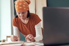 Female carpenter doing financial calculation stock image