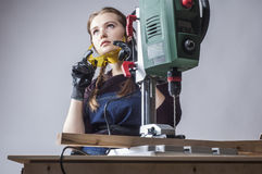 Female carpenter and drilling machine. Royalty Free Stock Photos