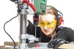 Female carpenter and drilling machine. Stock Images