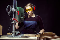 Female carpenter and drilling machine. Royalty Free Stock Images