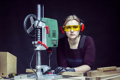 Female carpenter and drilling machine. Stock Image