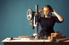 Female carpenter and drilling machine. Royalty Free Stock Photo