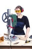 Female carpenter and drilling machine. Stock Photo
