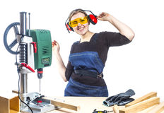 Female carpenter and drilling machine. Royalty Free Stock Image