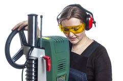 Female carpenter and drilling machine. Stock Photos
