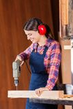 Female Carpenter Drilling Wood In Bandsaw Stock Images
