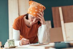 Female carpenter with financial problems. In carpentry woodwork workshop royalty free stock photos