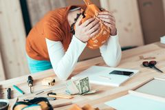 Female carpenter with financial problems. Female carpenter with head kerchief with financial problems in carpentry woodwork workshop, selective focus royalty free stock photography