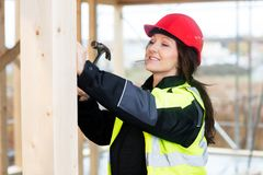 Female Carpenter Hammering Nail In Wood At Site Stock Image